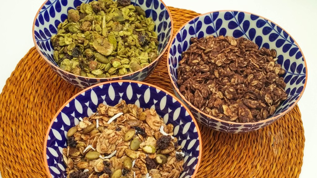 three bowls of granola with the following flavours - cranberry matcha, peanut butter and chocolate and spiced