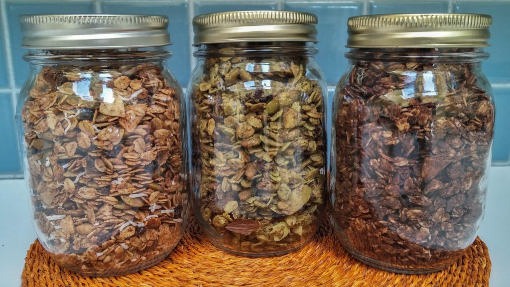 three jars of granola with the following flavours - cranberry matcha, peanut butter and chocolate and spiced