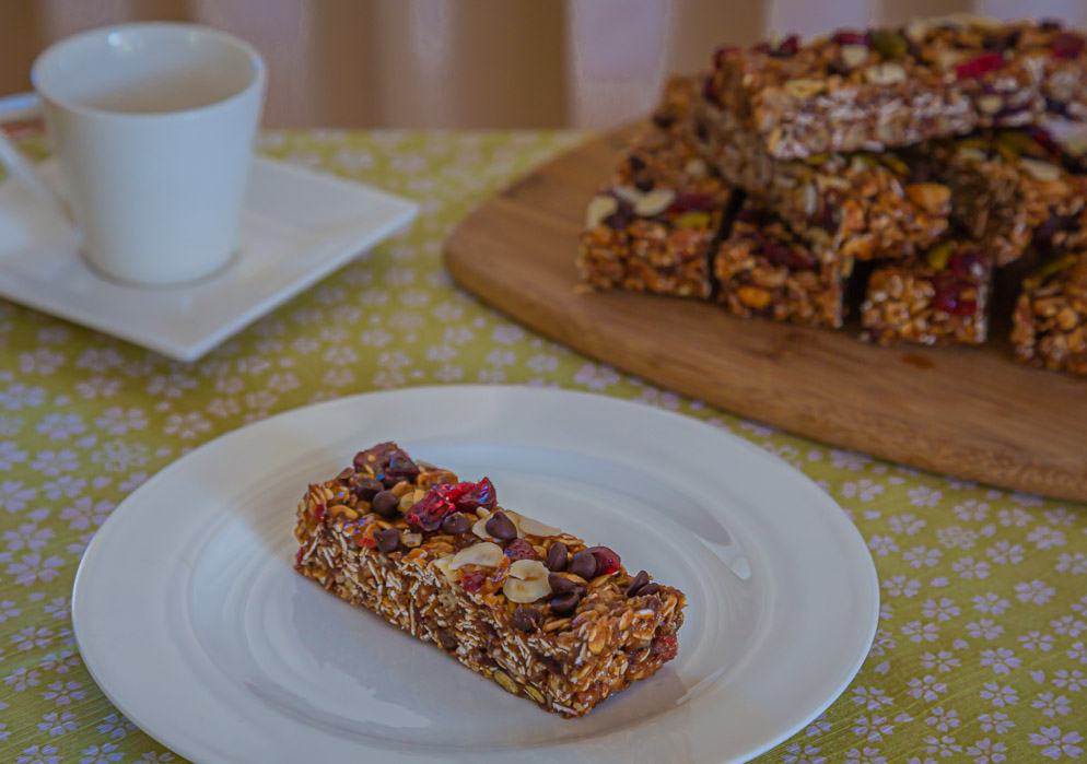 healthy no bake chewy granola bars piled on a board and one bar on a plate