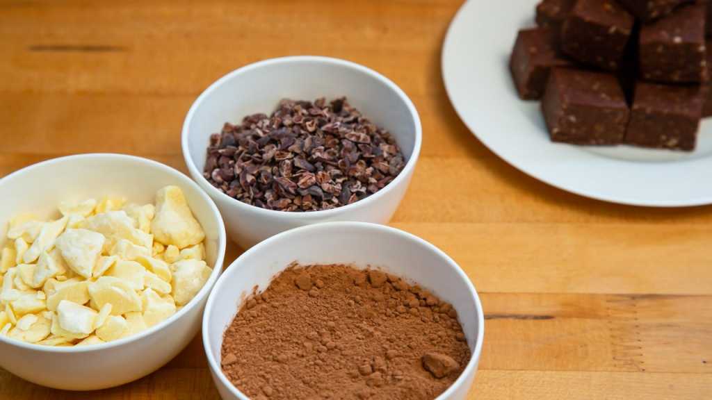 three bowls containing cacao butter, cacao powder and cacao nibs and plate of brownies
