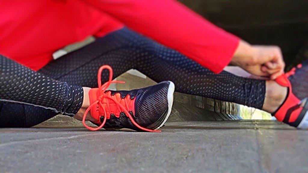image of female in workout gear  sitting down and tying shoe laces