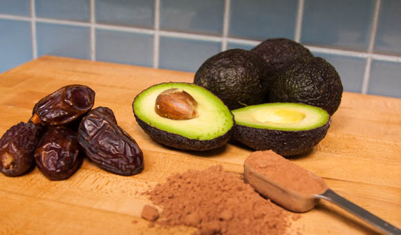 chopping board with ingredients for chocolate avocado mousse - medjool dates, avocado, cacao powder