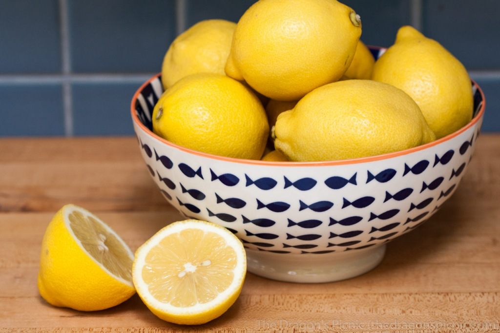 blue and white bowl full of lemos and cut up lemon in front