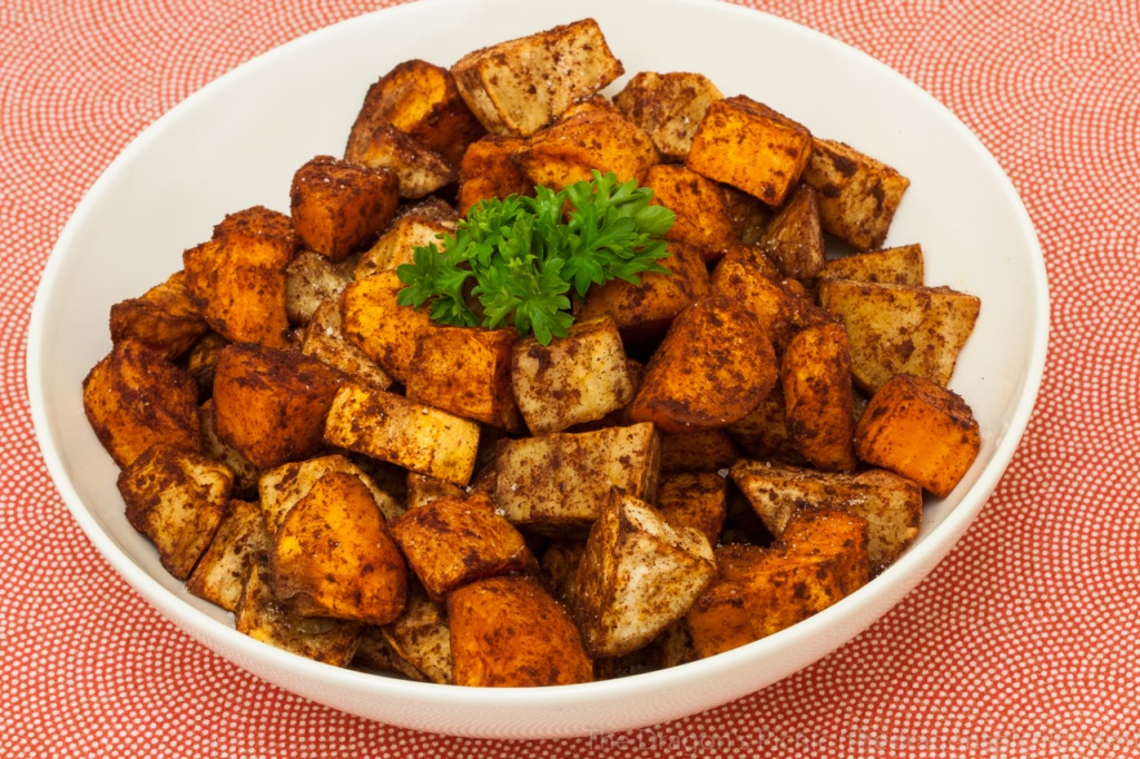 Bowl of mixed orange, white and purple sweet potatoes, roasted with paprika and cinnamon.