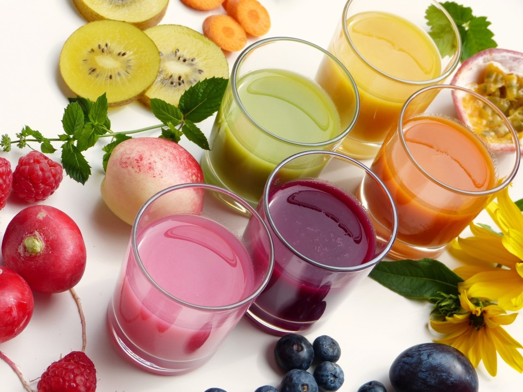 five glasses of juice in different colours - yellow, orange, purple, green and pink