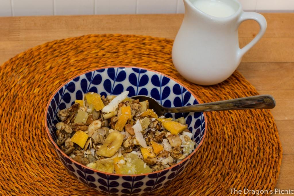 bowl of tropical granola with milk jug