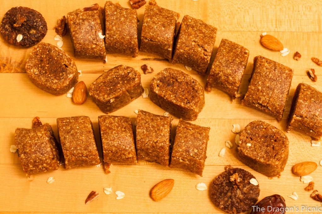 Image of fig rolls on cutting board with decorative dates, figs, almonds, oats, and pecans