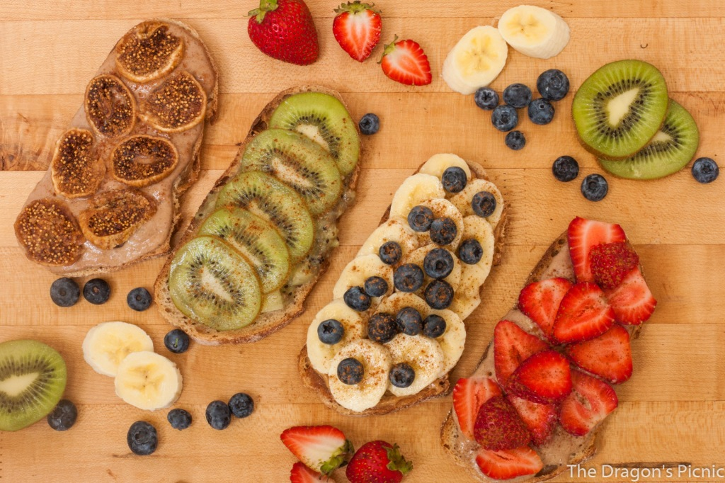 board with toasts with different toppings - dried figs, kiwi, banana and blueberry, strawberry