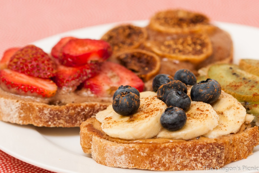 plate of toasts with different toppings - dried figs, kiwi, banana and blueberry, strawberry