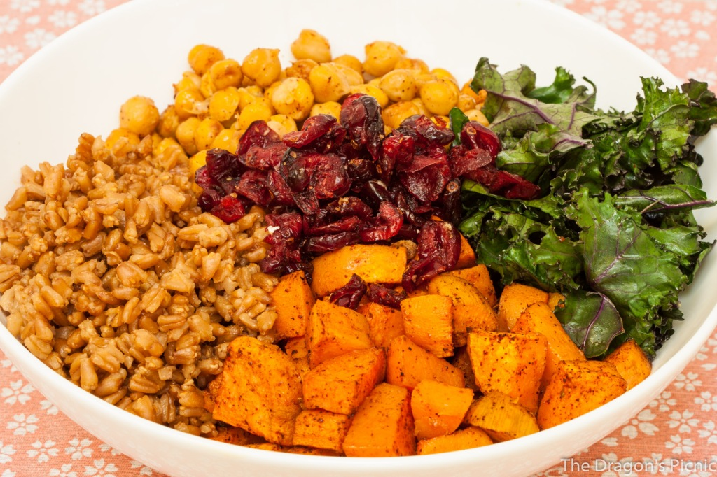 bowl with farro, kale and roasted sweet potato salad ingredients - kale, chickpeas, farro, sweet potato and cranberries