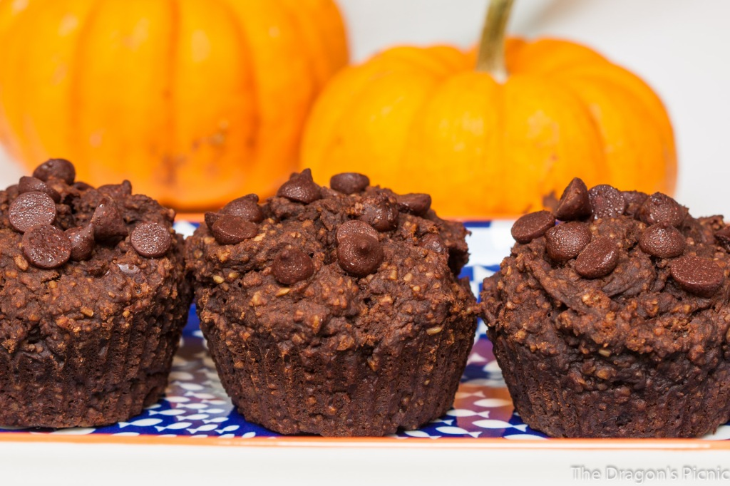 close up of three chocolate pumpkin muffins with two pumpkins in background