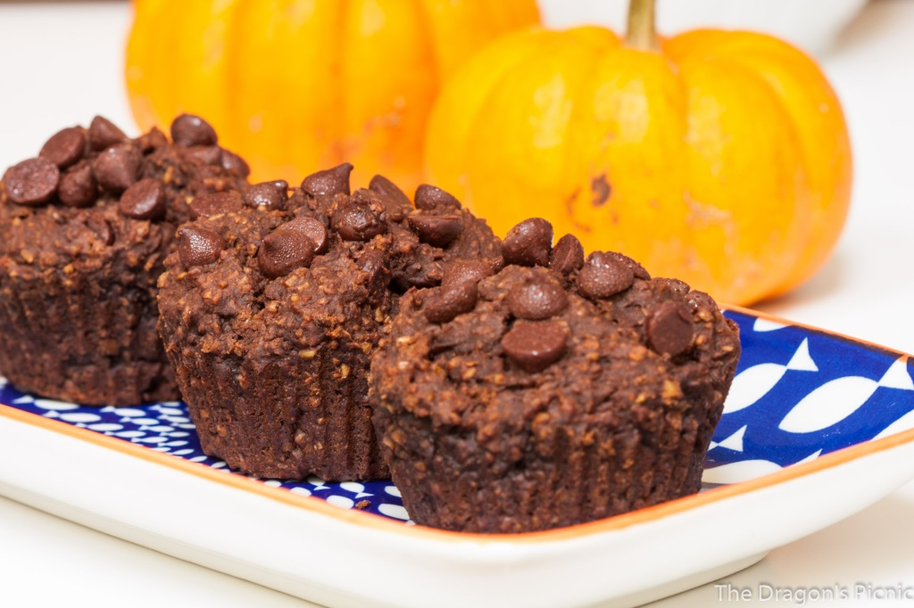 close up of three chocolate pumpkin muffins with pumpkins in the background