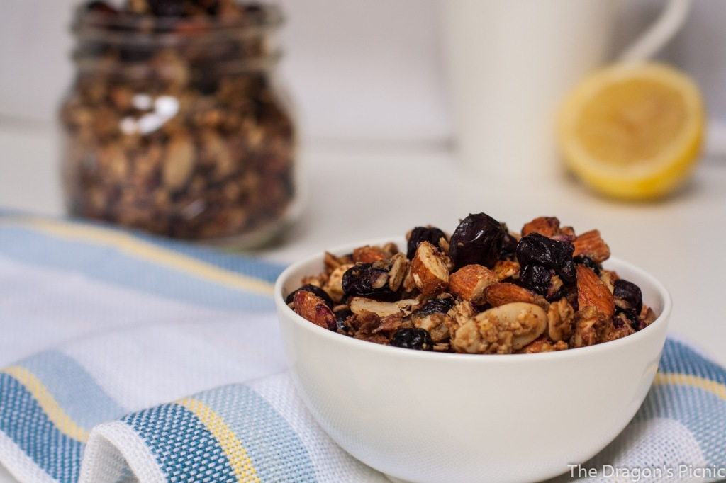 Bowl of double blueberry, lemon, almond granola with jar in background