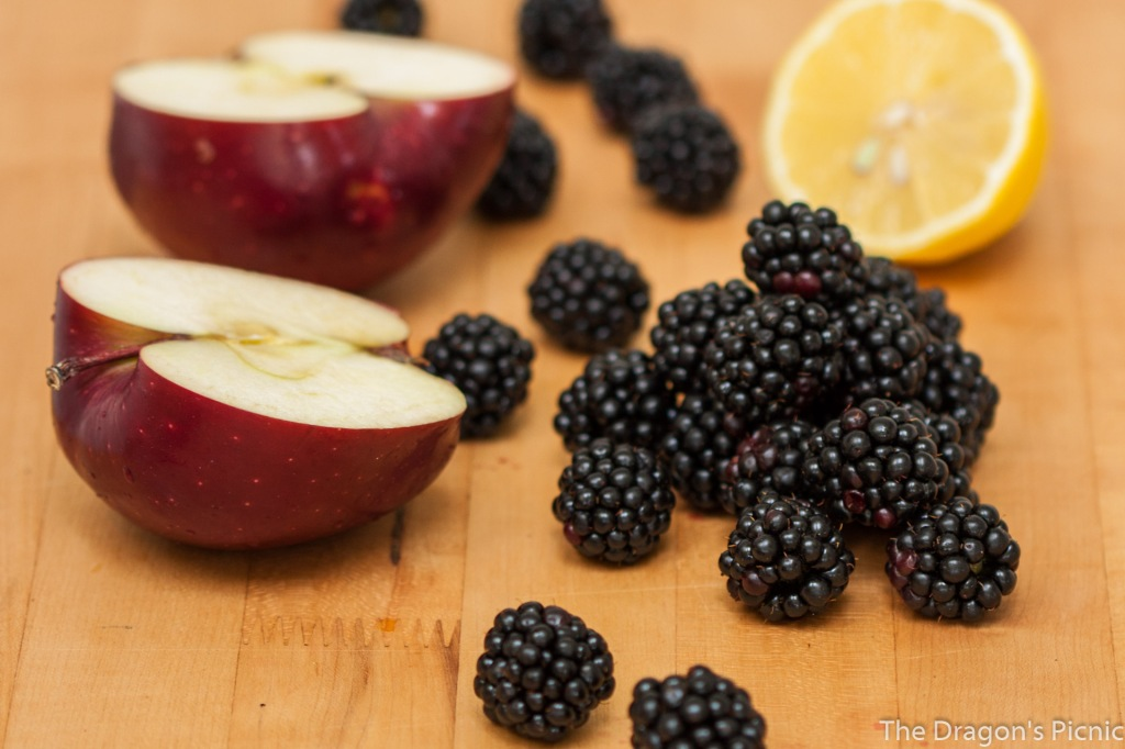 chopping board with blackberries, lemon and a chopped apple