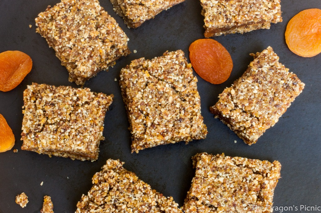 aerial view of black plate with several apricot and peanut bars and dried apricots