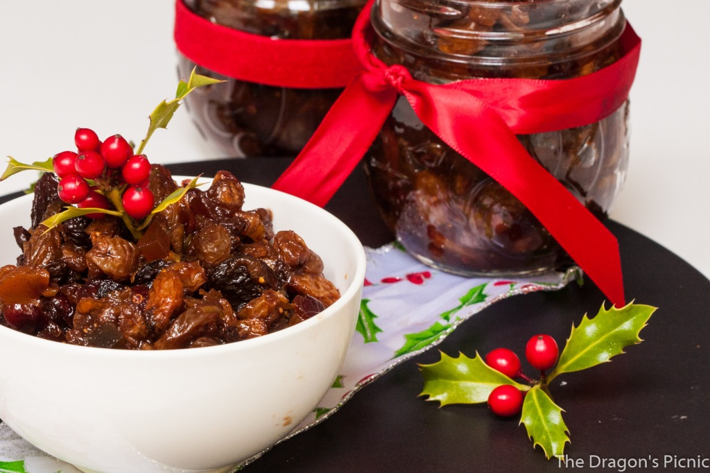 two jars and small white bowl of mincemeat with holly and Christmas decorations