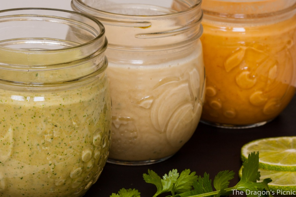 Close up of three jars of lime-based tahini sauces: lime cilanto, ginger lime and spicy lime.