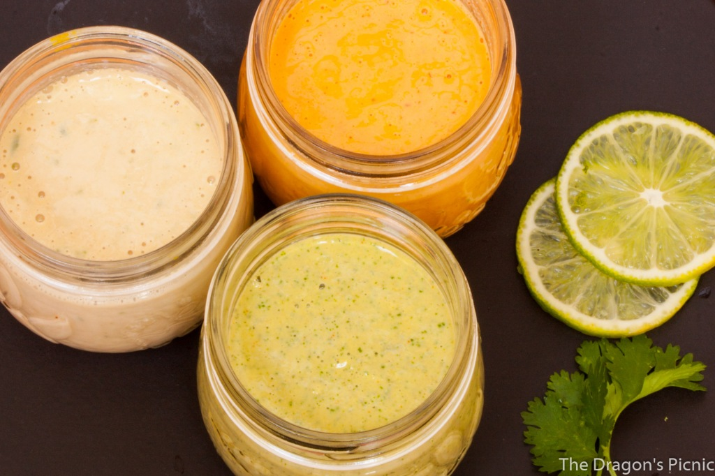 Arial view of Three jars of lime-based tahini sauces: lime cilanto, ginger lime and spicy lime.