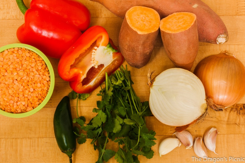 cutting board with bowl of red lentils and chopped vegetables including sweet potato, red pepper, jalapeno pepper, onion , garlic and cilantro