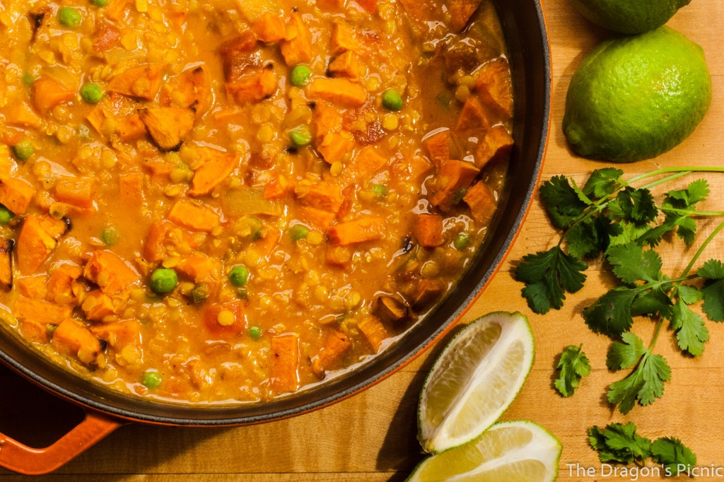 arial view of pot of red lentil and sweet potato stew with limes and cilantro on the side