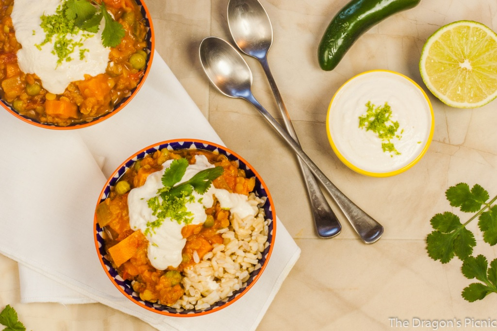 arial view of two bowls of red lentil and sweet potato stew with dish of cashew coconut lime cream, pepper and cut lime in background
