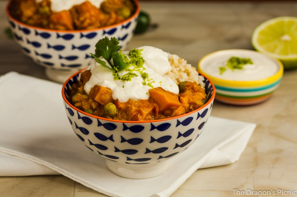 two bowls of red lentil and sweet potato stew with dish of cashew coconut lime cream, pepper and cut lime in background