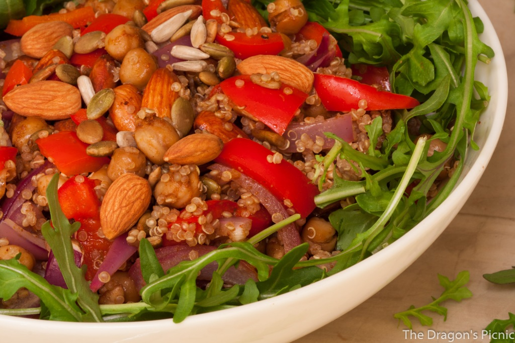 close up of white bowl with spiced almond and quinoa salad on bed of arugula