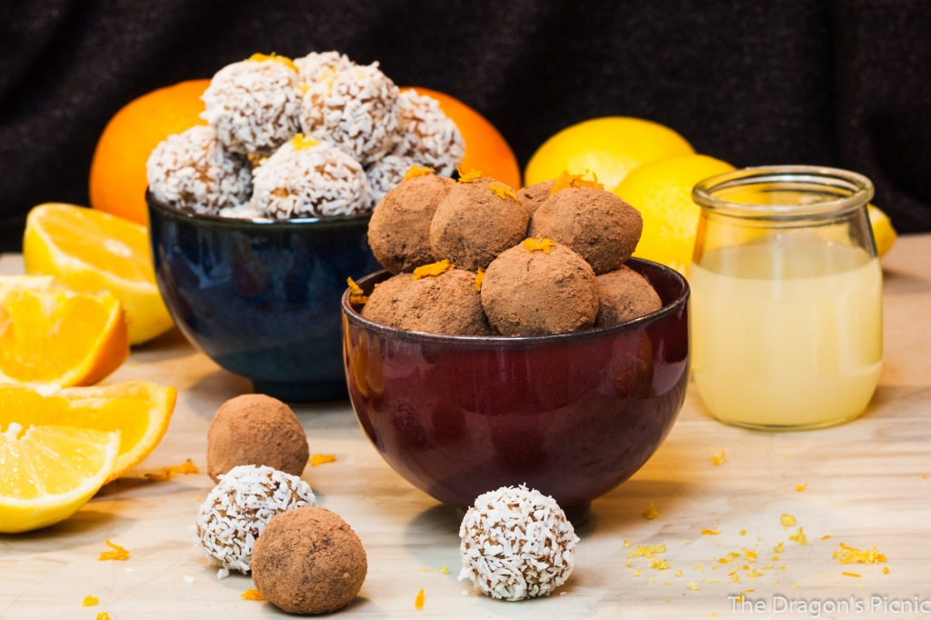 two bowls piled high with orange chocolate and lemon coconut sweets with lemons and oranges in background
