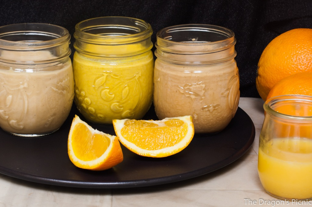 3 jars of orange tahini based sauces with orange segments in foreground and oranges in background