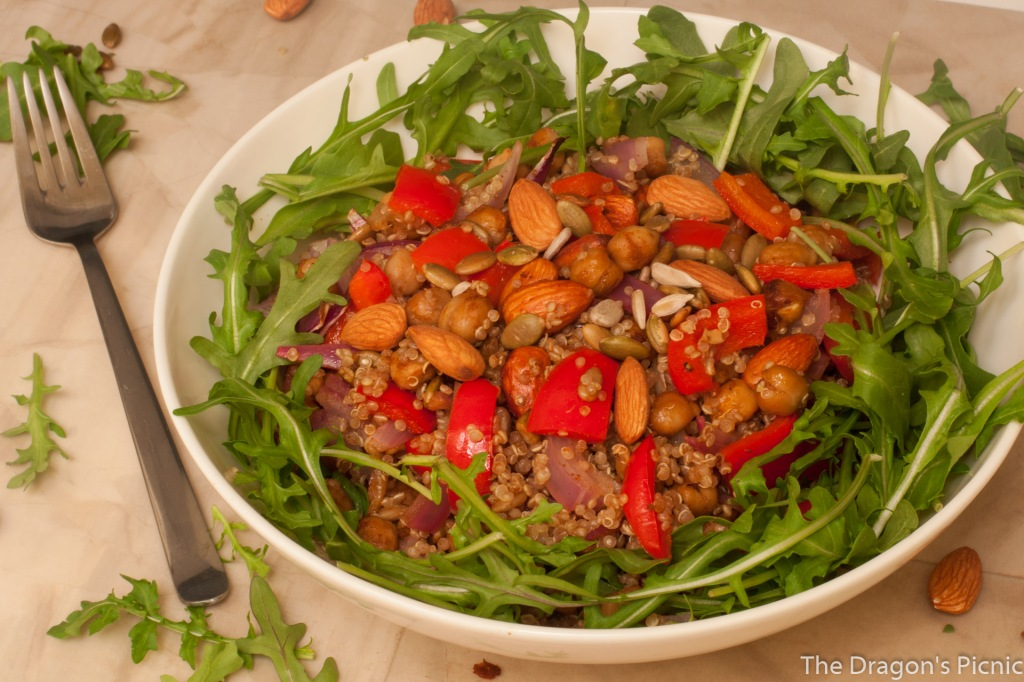 white bowl with spiced almond and quinoa salad on bed of arugula and fork on the side