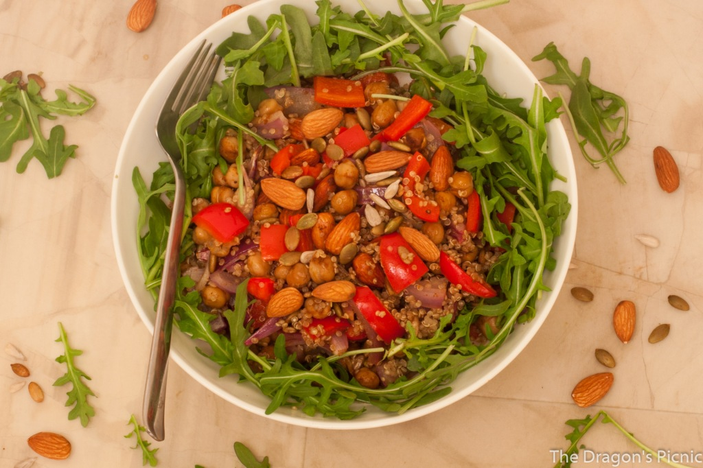 white bowl with spiced almond and quinoa salad on bed of arugula with fork resting in bowl